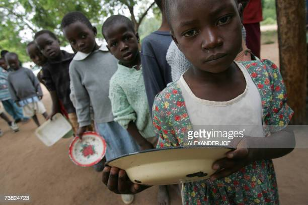 Zimbabwean children wait for food 02 April 2007 at the Masarira primary school where about 30 pupils receive a daily ration of beans and starchbased...