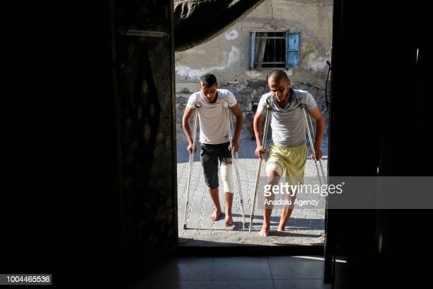 Bilal and Said Diyab try to walk with crutches after Israeli forces opened fire on demonstrators and their siblings Muhammed and Ahmed Diyab while...