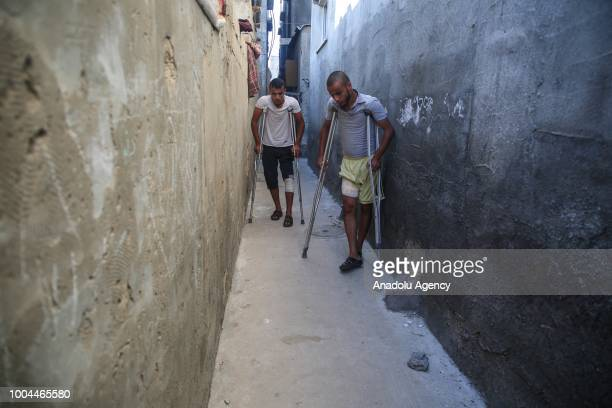 Bilal and Said Diyab try to walk with crutches and a wheelchair after Israeli forces opened fire on them and their siblings Muhammed and Ahmed Diyab...