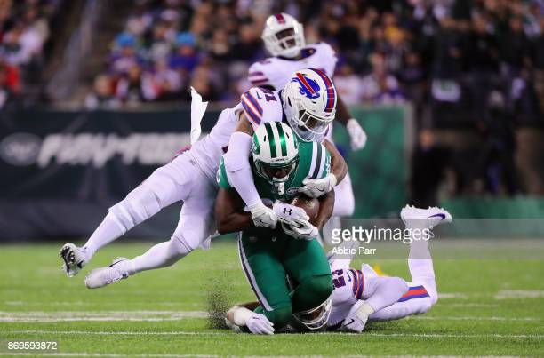 Bilal Powell of the New York Jets is taken down by Micah Hyde and Jordan Poyer of the Buffalo Bills during the third quarter of the game at MetLife...