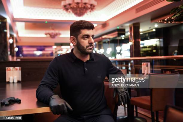 Bilal Sheikh owner of the Kebabish Grill restaurant in Glasgow sits in his empty restaurant on March 23 2020 as the it continues to operate as a...