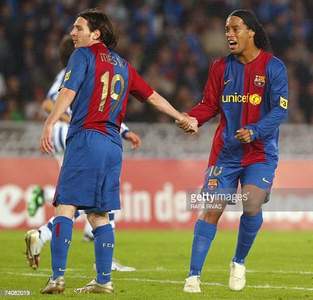 Barcelona's Brazilian Ronaldinho pulls Argentinian Lionel Messi's arm during a Spanish league football match against Real Sociedad at Anoeta stadium...