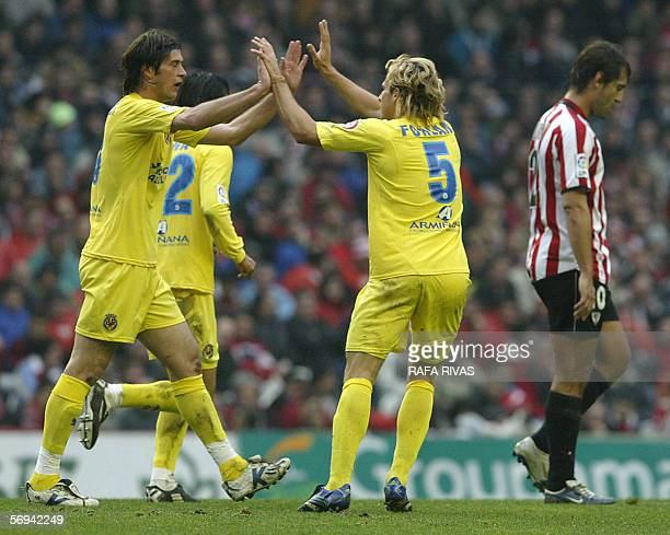 Villarreal Uruguayan Diego M Forlan celebrates a goal with teammate Italian Alessio Tacchinardi as Athletic Bilbao's Ismael Urzaiz reacts during a...