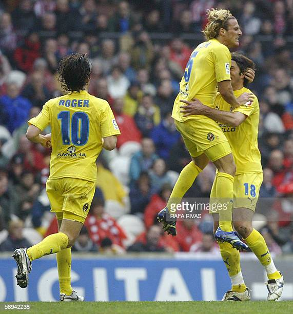 Villarreal's Uruguayan Diego M Forlan celebrates a goal with teammates Italian Alessio Tacchinardi and Roger Garcia during their Spanish league...