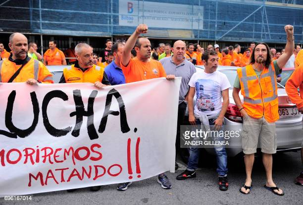 Bilbao's dockers gesture as they hold a banner reading Struggle We will die killing during a twoday strike at the Port of Bilbao in the Spanish...