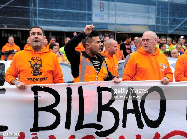 Bilbao's dockers stand behind a banner during a two-day strike at the Port of Bilbao, in the Spanish Basque city of Santurtzi on June 15, 2017....