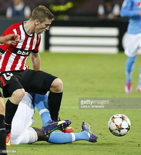 Bilbao's Spanish forward Iker Muniain fights for the ball with Napoli's defenders during the first leg of the UEFA Champions League play off football...
