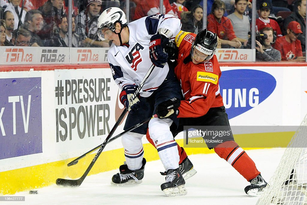Bill Arnold #14 of Team USA battles for the puck with Gaetan Haas #11 of Team Switzerland during the 2012 World Junior Hockey Championship Relegation game at the Scotiabank Saddledome on January 4, 2012 in Calgary, Alberta, Canada. Team USA defeated Team Switzerland 2-1.