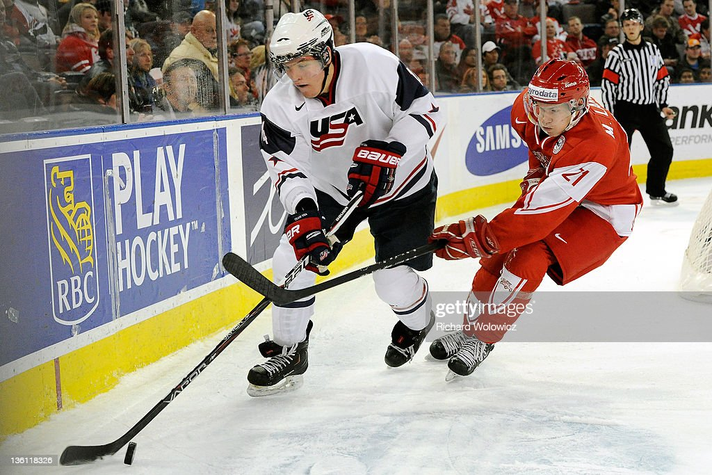 Bill Arnold #14 of Team USA skates with the puck while being defended by Mark Larsen #21 of Team Denmark during the 2012 World Junior Hockey Championship game at Rexall Place on December 26, 2011 in Edmonton, Alberta, Canada.