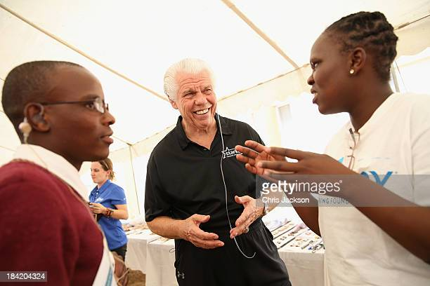 Bill Austin of the Starkey Foundation helps a young boy feel the vibration of her voice as she fits a hearing aid at Lesotho Cooperative College on...