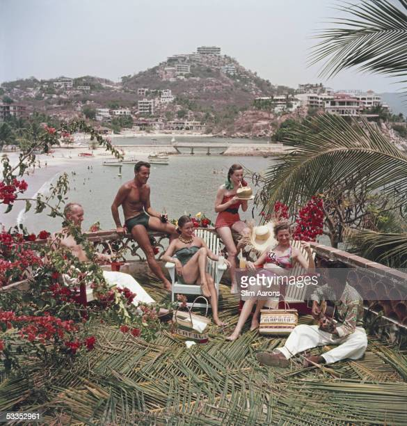 Bill Babb Thomas Beecher model Carolyn Phillips Mrs Rabb and model Jean Adams enjoying some guitar music on a terrace in Acapulco Mexico 1952 The...
