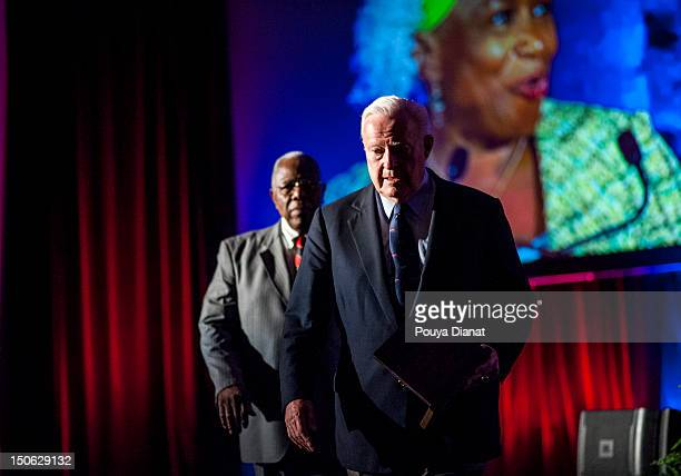 Bill Bartholomay and Hall of Famer Hank Aaron walk off the stage at the 2012 MLB Beacon Awards Luncheon presented by Belk during the Delta Civil...