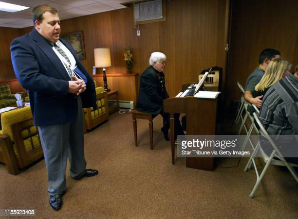 Bill Bauman left owner of Bauman Family Funeral Homes in northern Minnesota closes his eyes in prayer during services for a deceased member of the...
