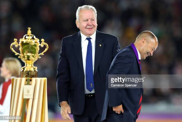 Bill Beaumont Chairman of World Rugby looks on as Eddie Jones Head Coach of England reacts as he walks past the Web Ellis cup after collecting his...
