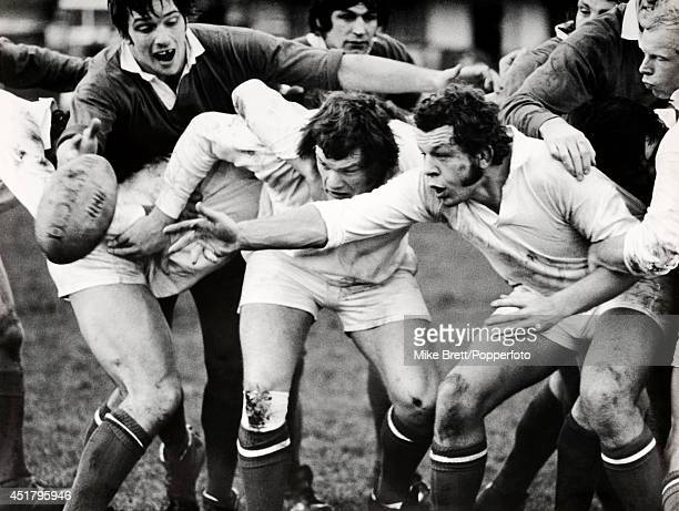 Bill Beaumont of the North passes back protected by teammate Fran Cotton while Nigel Horton of the Midlands tries to break through during the Final...