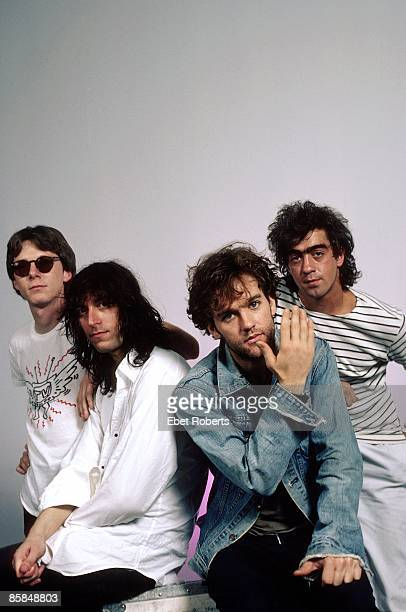 Photo of Bill BERRY and Michael STIPE and Peter BUCK and Mike MILLS and REM LR Mike Mills Peter Buck Michael Stipe Bill Berry posed studio group shot