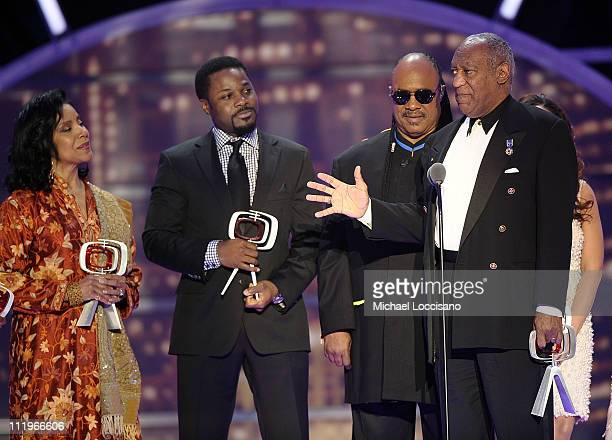 Bill Cosby accepts the Impact Award onstage with presenter Stevie Wonder and Cosby Show cast members Phylicia Rashad and Malcolm-Jamal Warner at the...