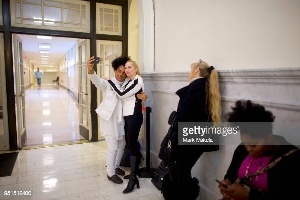 Bill Cosby accusers Lili Bernard and Caroline Heldman pose for a selfie while waiting in line before the courtroom opens at the Montgomery County...