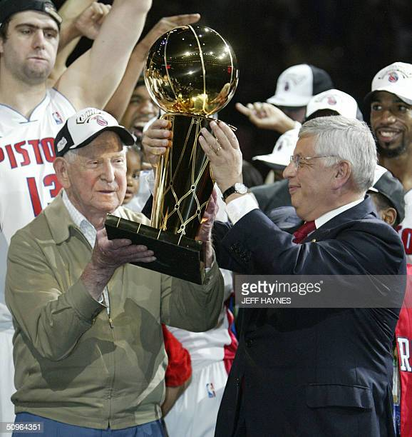 Bill Davidson the owner of the Detroit Pistons gets the Larry O'Brien trophy from Commissioner David Stern after beating the Los Angeles Lakers in...