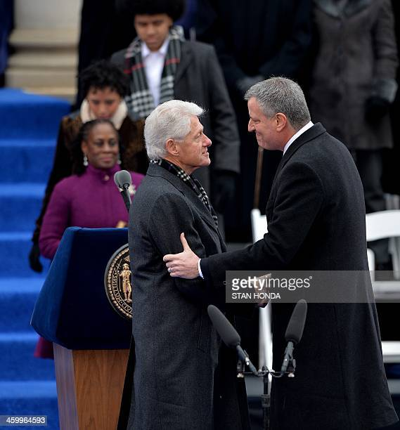 Bill de Blasio just before being sworn in as New York City Mayor shakes hands with former US President Bill Clinton on the steps of City Hall in...