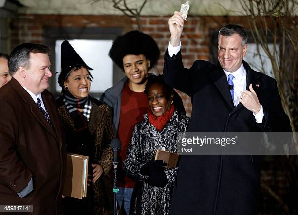 Bill de Blasio produces the $9 fee for City Clerk Michael McSweeney after he signed the oath of office as his wife Chirlane McCray and children Dante...