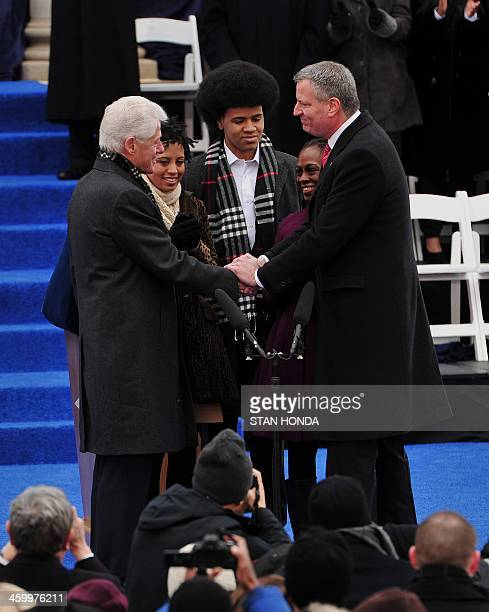 Bill de Blasio reacts after being sworn in as New York City Mayor by former US President Bill Clinton shakes hands on the steps of City Hall in Lower...