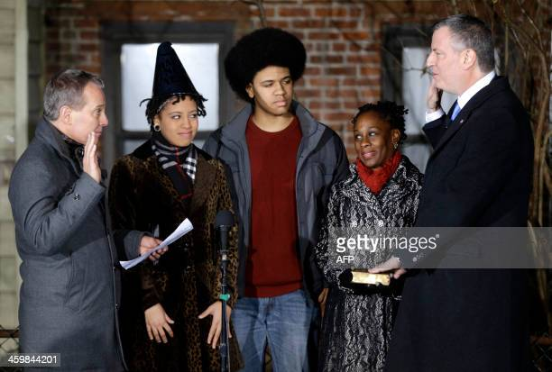 Bill de Blasio right is sworn in as the mayor of New York City by State Attorney General Eric Schneiderman left while his family Chiara de Blasio...