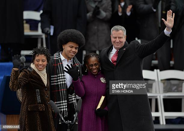 Bill de Blasio waves after being sworn in as New York City Mayor on the steps of City Hall in Lower Manhattan January 1 2014 in New York with his...