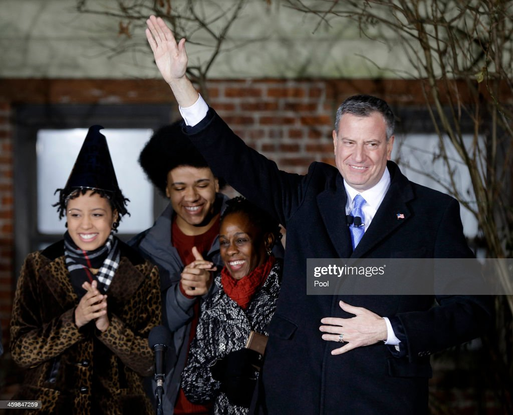Bill de Blasio waves whilst standing with his family (from left) Chiara de Blasio, Dante de Blasio and wife Chirlane McCray after being sworn in as mayor of New York City after midnight January 1, 2014 in the Park Slope neighborhood of the Brooklyn borough of New York City. De Blasio took the oath outside his home in Park Slope. His inauguration will be celebrated at noon today on the steps of City Hall when he takes the oath again, which will be administered by former U.S. President Bill Clinton.