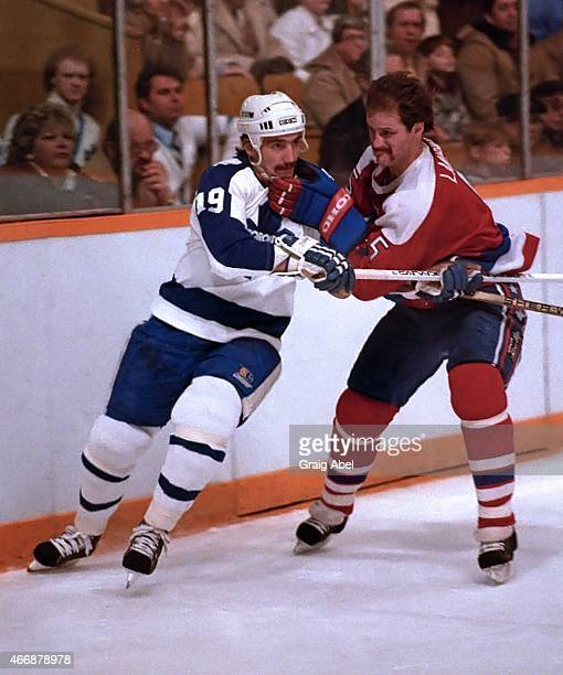 Bill Derlago of the Toronto Maple Leafs is held up by Rod Langway of the Washington Capitals at Maple Leaf Gardens in Toronto Ontario Canada on...