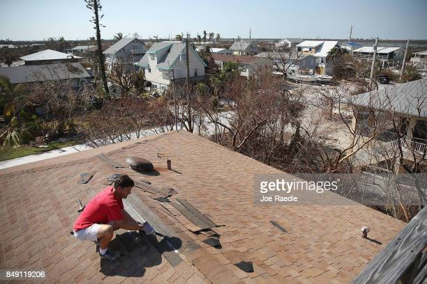 Bill Evans replaces shingles that were blown off the roof when Hurricane Irma passed through on September 18 2017 in Cudjoe Key Florida The process...