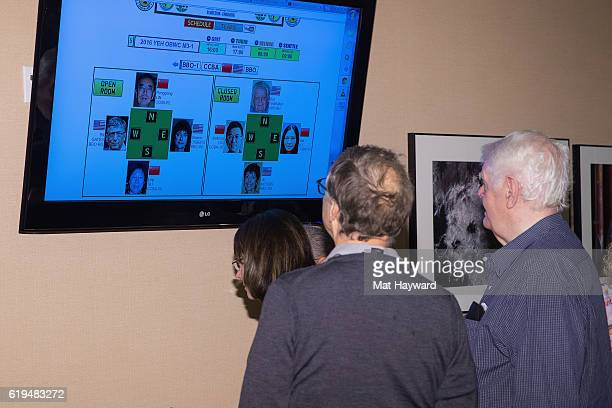 Bill Gates and alltime world top ranked Bridge player Bob Hamman look at a screen showing their tournament spots before they participate in the first...