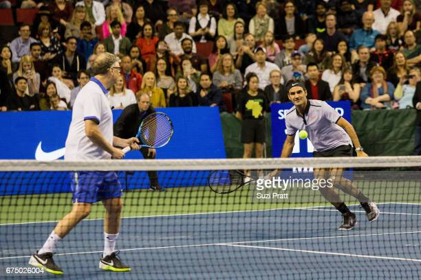 Bill Gates and Roger Federer of Switzerland in action against Mike McCready and John Isner of the United States at the Match For Africa 4 exhibition...
