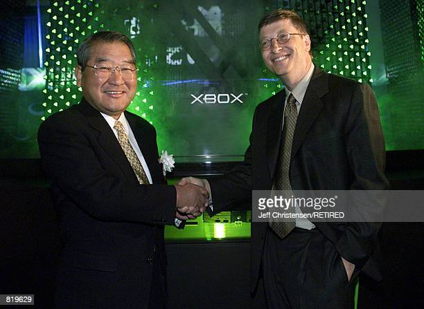 Bill Gates, Chairman and Chief Software Architect of Microsoft, shakes hands with Kenzo Tsujimoto, vice chairman of the Computer Entertainment...