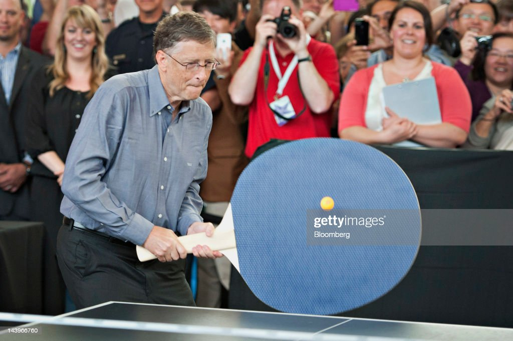 Bill Gates, chairman of Microsoft Corp., holds a large ping pong paddle as he plays table tennis with Ariel Hsing, a member of the 2012 U.S. Olympic team, during an event at the annual shareholders meeting in Omaha, Nebraska, U.S., on Sunday, May 6, 2012. Berkshire Hathaway Inc. investment managers Todd Combs and Ted Weschler receive $1 million salaries and can earn more if their bets beat the Standard & Poor's 500 Index, Buffett said Sunday. Photographer: Daniel Acker/Bloomberg via Getty Images