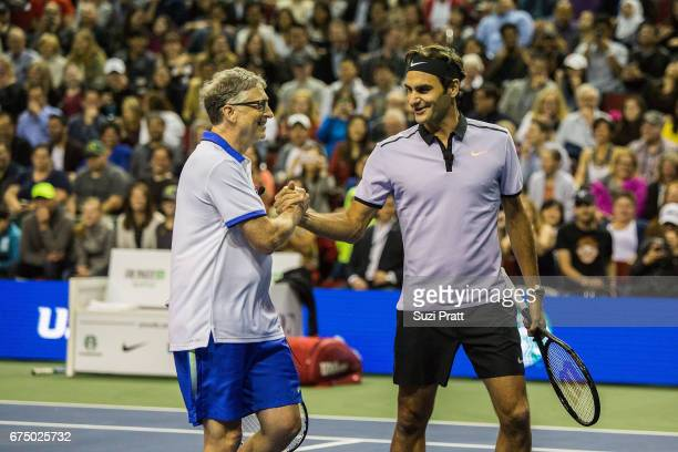 Bill Gates shakes hands with Roger Federer at the Match For Africa 4 exhibition match at KeyArena on April 29 2017 in Seattle Washington