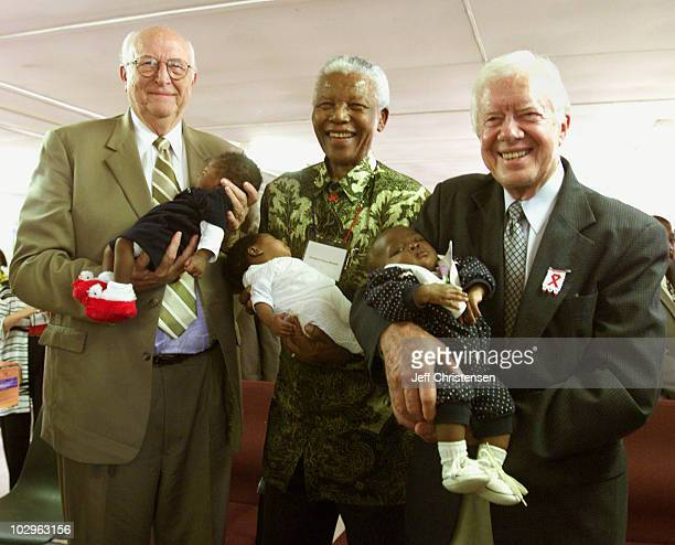 Bill Gates Sr. , former South African President Nelson Mandela and former U.S. President Jimmy Carter hold babies at the Zola clinic in the Soweto...