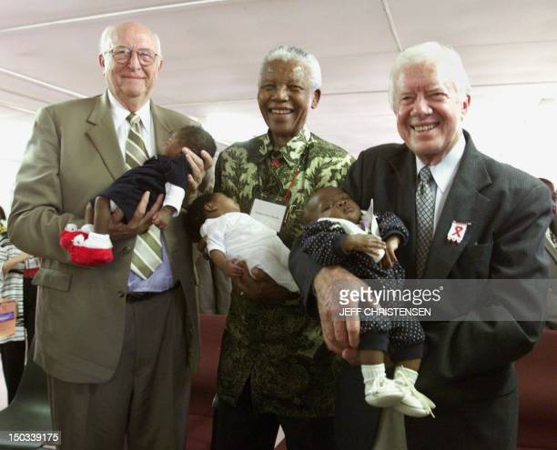 Bill Gates Sr., former South African President Nelson Mandela and former U.S. President Jimmy Carter hold babies at the Zola clinic, in the Soweto...