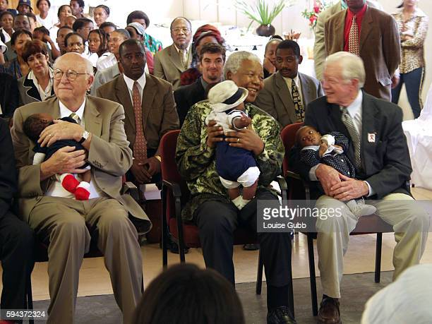 Bill Gates Sr., Nelson Mandela and former US President Jimmy Carter cuddle babies born of HIV positive mothers at a Zola clinic function. They are...