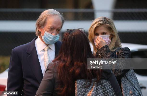 Bill Gross, co-founder of Pacific Investment Management Co. , and his girlfriend Amy Schwartz wear protective masks while departing from state court...