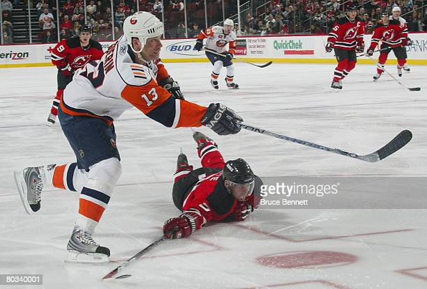 Bill Guerin of the New York Islanders shoots past a diving Colin White of the New Jersey Devils on March 21 2008 at the Prudential Center in Newark...