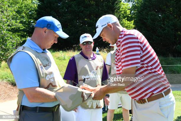 Bill Haas autographs caddie bibs for members of the Arm Forces during the ProAm round for the Quicken Loans National at TPC Potomac at Avenel Farm on...