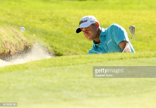 Bill Haas hits out of a bunker on the 17th hole during the third round of the Northern Trust Open at Riviera Country Club on February 16 2013 in...