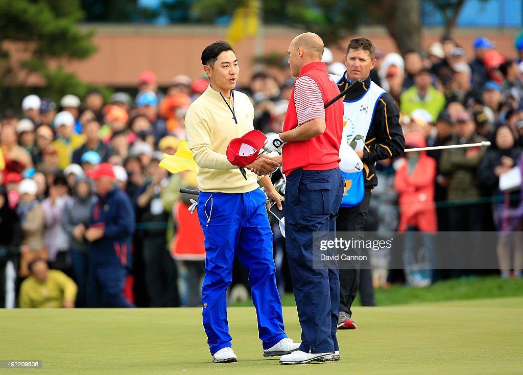 Bill Haas of the United States team shakes hands with Sangmoon Bae of South Korea and the International team after Haas won the final match on the 18th green during the Sunday singles matches in the 2015 Presidents Cup at the Jack Nicklaus Golf Club Korea on October 11, 2015 in Incheon, South Korea.