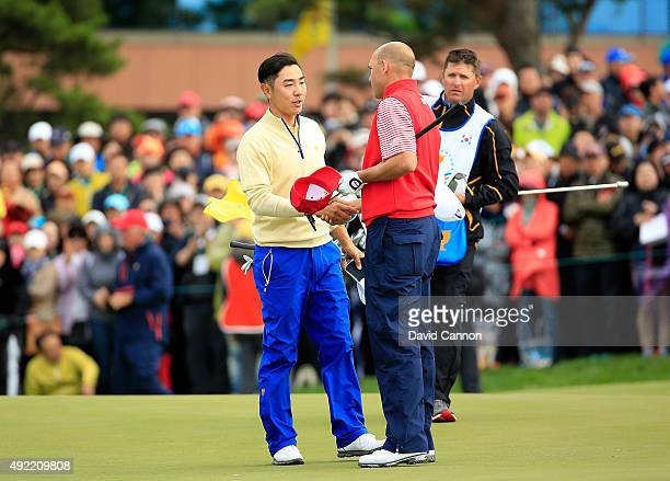 Bill Haas of the United States team shakes hands with Sangmoon Bae of South Korea and the International team after Haas won the final match on the...