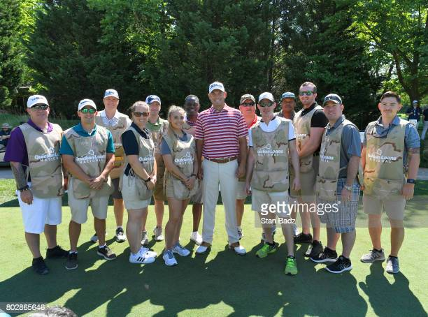 Bill Haas poses for a group shot with members of the Arm Forces during military caddie day during the ProAm round for the Quicken Loans National at...