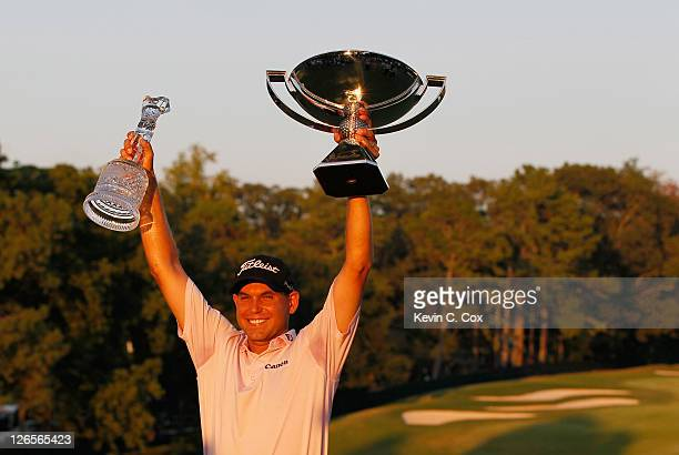 Bill Haas poses on the 18th green after winning won both the TOUR Championship and the FedExCup after the final round of the TOUR Championship at...
