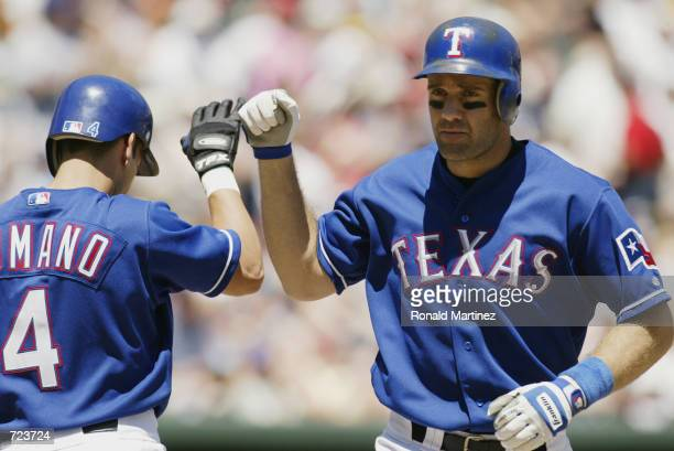 Bill Haselman and Jason Ramano both of the Texas Rangers celebrate during the game against the Kansas City Royals at The Ballpark in Arlington Texas...