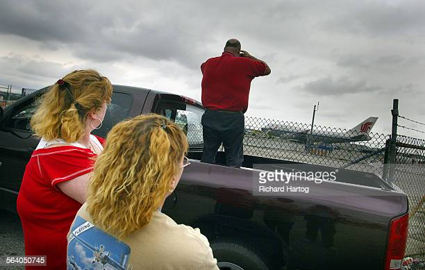 Bill Herold of Hawthorne stands in the back of his truck to snap a photo of an Air China jumbo jet that apparently turned too sharply while taxiing...