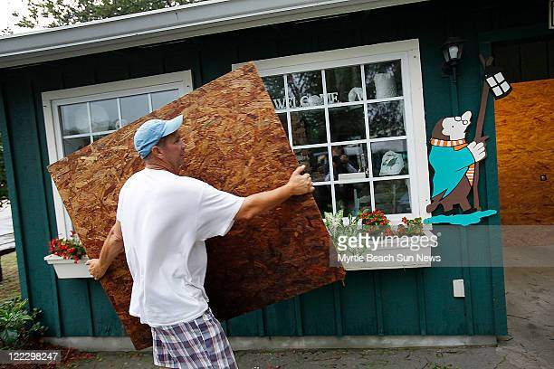 Bill Jennings removes protective plywood from a store window at the Mole Hole in Pawleys Island South Carolina Saturday August 27 after Hurricane...